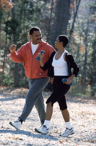 Middle-aged couple power walking together